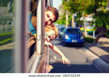 father and son traveling in public bus without windows, through asian city - stock photo