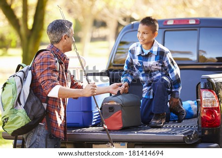 Father And Son Unpacking Truck On Camping Holiday - stock photo