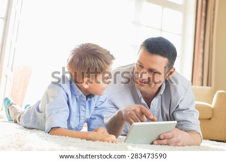 Father and son using digital table on floor at home
