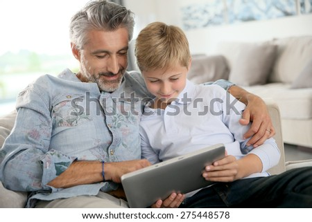 Father and son using digital tablet at home - stock photo