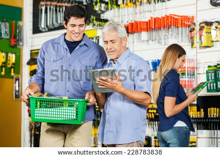 Father and son using digital tablet in hardware store with female customer in background - stock photo