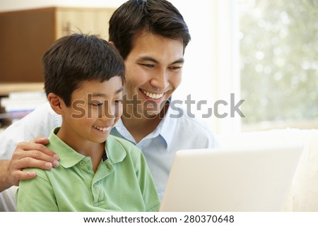 Father and son using laptop - stock photo