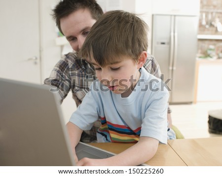 Father and son using laptop at table in house - stock photo