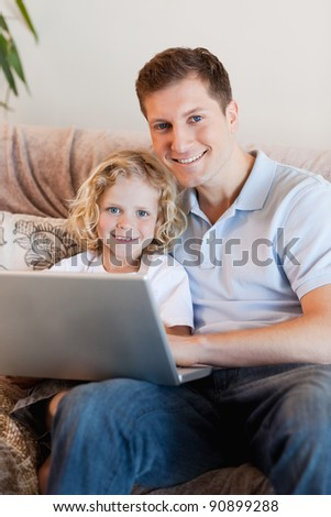 Father and son using laptop on the sofa