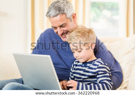 Father and son using laptop on the sofa in living room