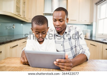 Father and son using tablet in the kitchen