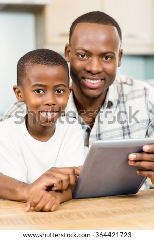 Father and son using tablet together in the kitchen