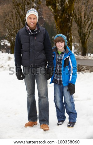 Father And Son Walking Along Snowy Street In Ski Resort - stock photo