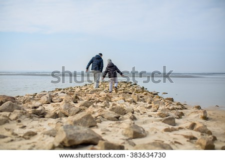 father and son walking along the rocks on the beach - stock photo