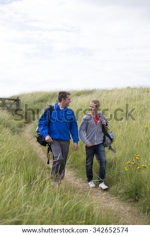 Father and son walking down the sandunes onto the beach. They are wearing warm casual clothing and smiling at each other. - stock photo