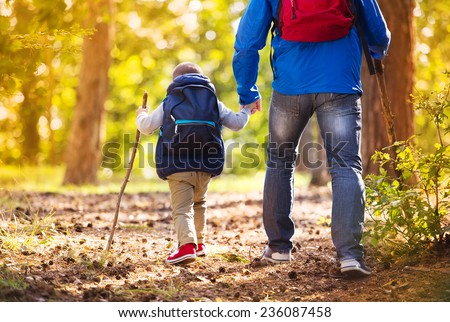 Father and son walking during the hiking activities in autumn forest at sunset - stock photo