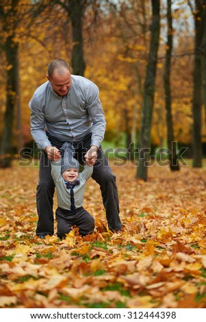 father and son walking in autumn forest - stock photo