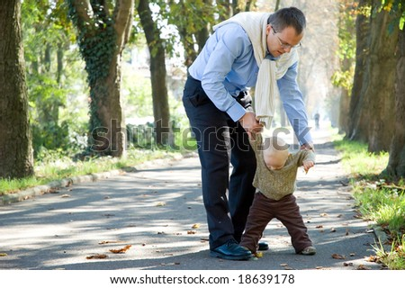 Father and son walking in park autumn