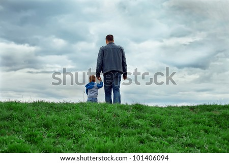 father and son walking into the future. rear view - stock photo
