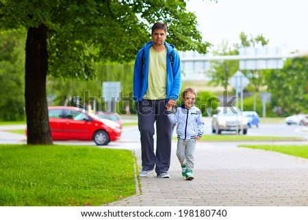 father and son walking on city street