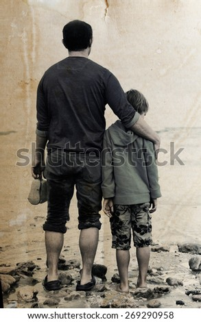 father and son walking on the beach - stock photo