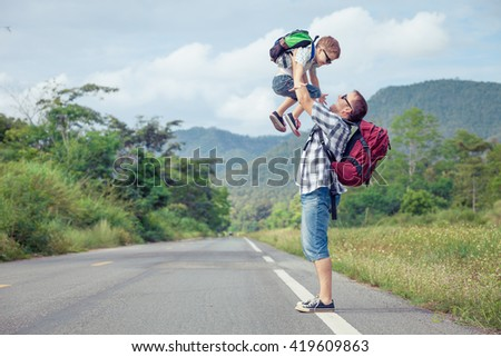 Father and son walking on the road at the day time.  Concept of friendly family.