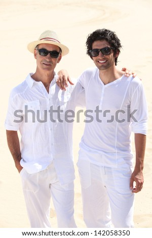 Father and son walking on the sand - stock photo