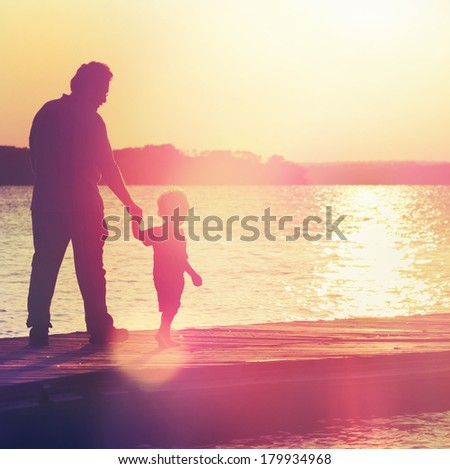 Father and son walking out on a dock at sunset - Instagram effect - stock photo