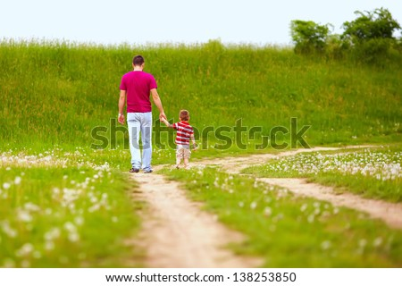 father and son walking rural footpath - stock photo