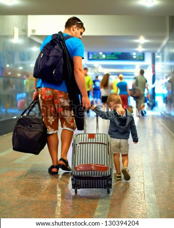 father and son walking through crowded  subway with huge luggage - stock photo