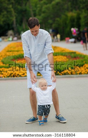Father and Son walking towards the camera.Baby taking first steps with father help in summer garden - stock photo