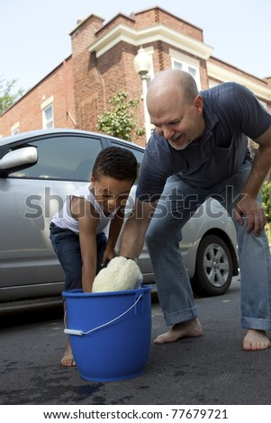 Father and son washing a car - stock photo