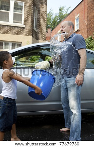 Father and son washing a car horseplay splashing