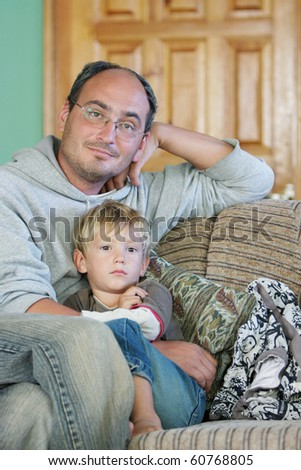 father and son watch tv at home - stock photo