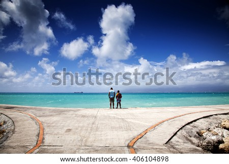 Father and son watching Caribbean sea from pier - Guadeloupe, Lesser Antilles