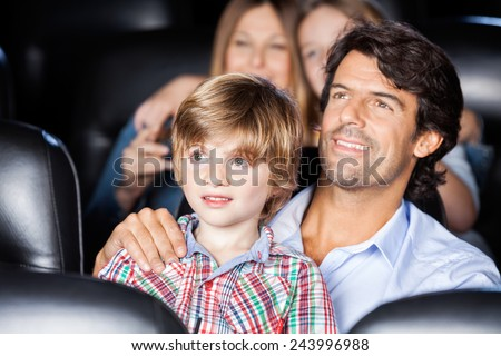Father and son watching film with family in movie theater - stock photo
