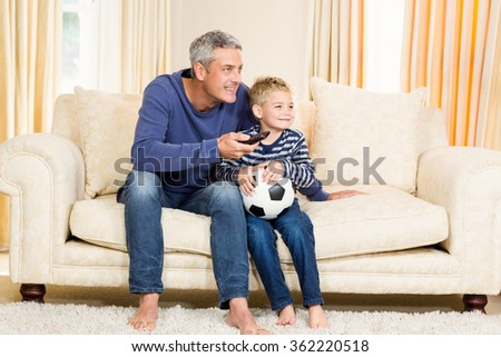 Father and son watching football match on tv sitting on the sofa