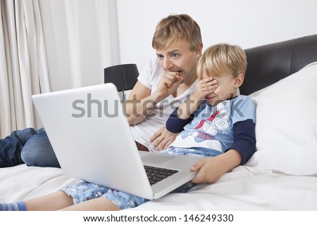 Father and son watching scary movie on laptop in bed