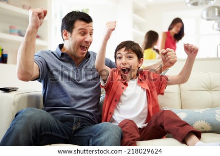 Father And Son Watching Sports On TV - stock photo