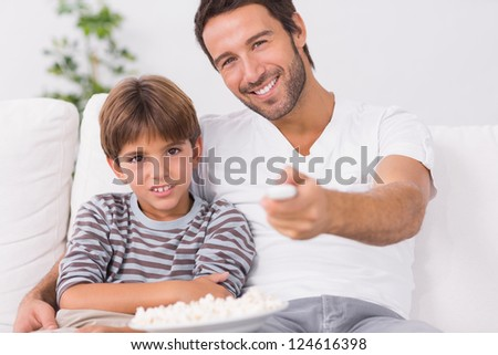 Father and son watching television together on the couch - stock photo