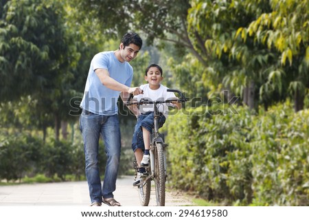 Father and son with a bicycle - stock photo