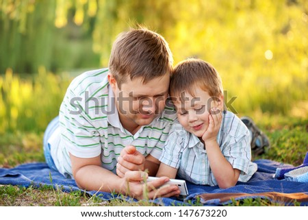 Father and son with a smartphone outdoors together - stock photo