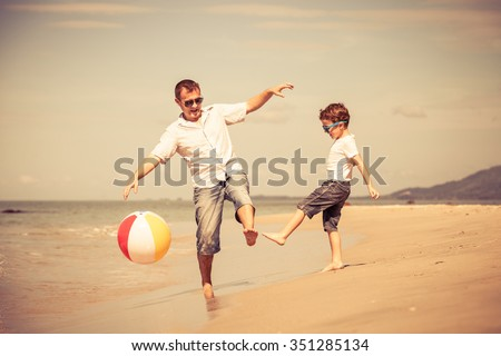 Father and son with ball playing soccer on the beach at the day time. Concept of friendly family. - stock photo