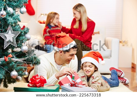 Father and son with gifts at christmas eve with mother and daughter on sofa
