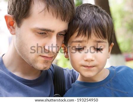 Father and son with interest looking at something together. Focus on boy