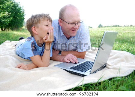 father and son with laptop outdoors - stock photo