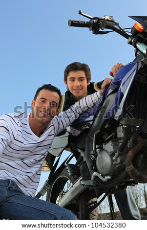 Father and son with motorcycle - stock photo