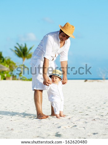 Father and son with panama hats having tropical vacation - stock photo