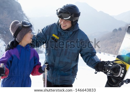 Father and Son with Ski Gear in Ski Resort