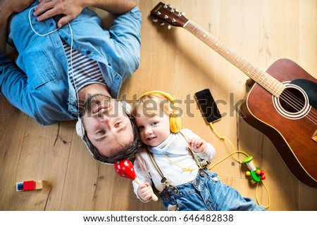 Father and son with smartphone and earphones, listening music.
