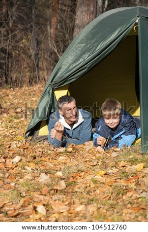father and son with tent in autumn forest - stock photo