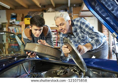 father and son working together on a classic car in a garage with air filter cover open looking in - stock photo