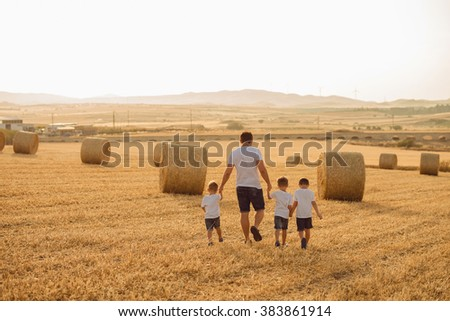 father and sons go hand in hand in the summer on a field with wheat - stock photo