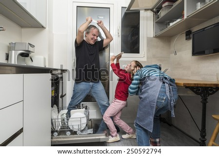 Father and sons joking while emptying the dishwasher - stock photo