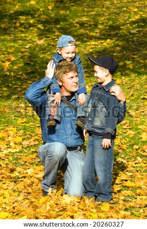 Father and sons on a bright autumn day - stock photo